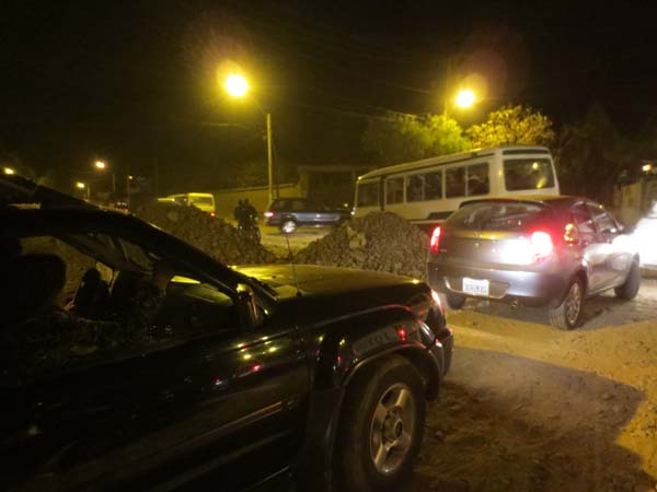 Cars moving in the night as piles of earth are removed from the road