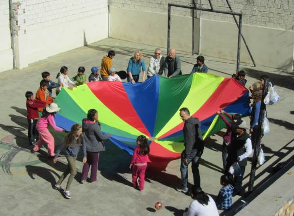 Children and adults around a parachute