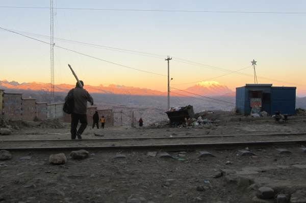 A man carrying a weight on his shoulder with mountains glowing in the sunset in the distance