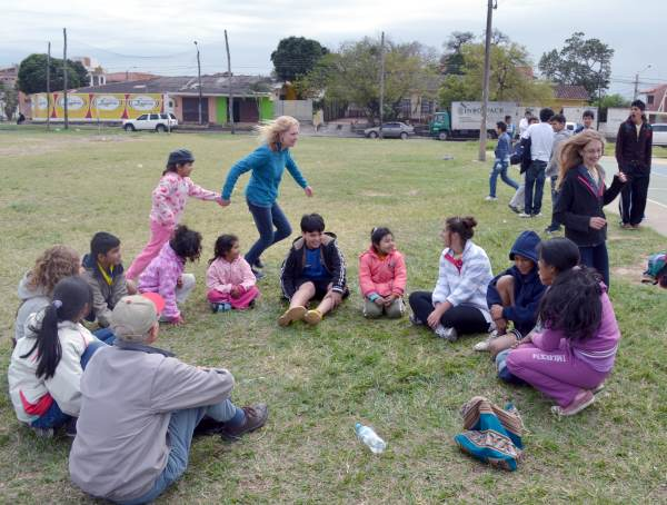 A game of duck duck goose, played sitting in a circle on the ground