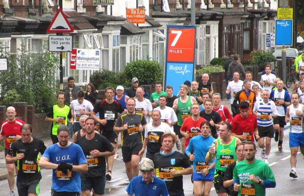 A crowd of runners going along a street lined with houses