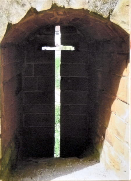 A picture of a narrow cross-shaped opening cut out of a wall
