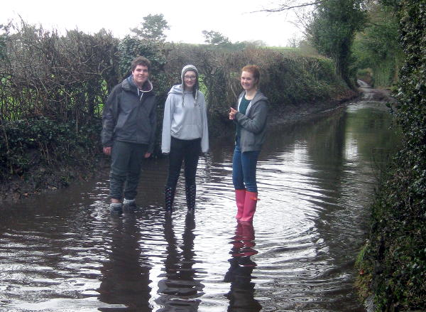 Reloaded members standing in a flooded road