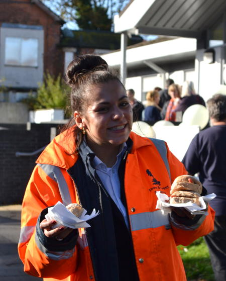 A steward holding bacon rolls