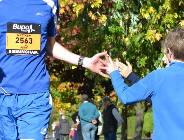 A young spectator high-fives a runner