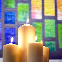 Candles in front of an artistic quilt