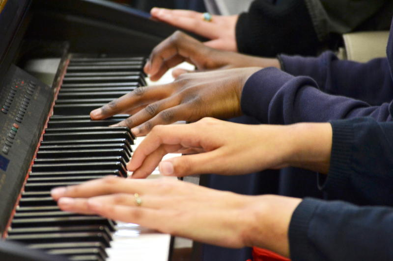 Multiple hands on a piano keyboard