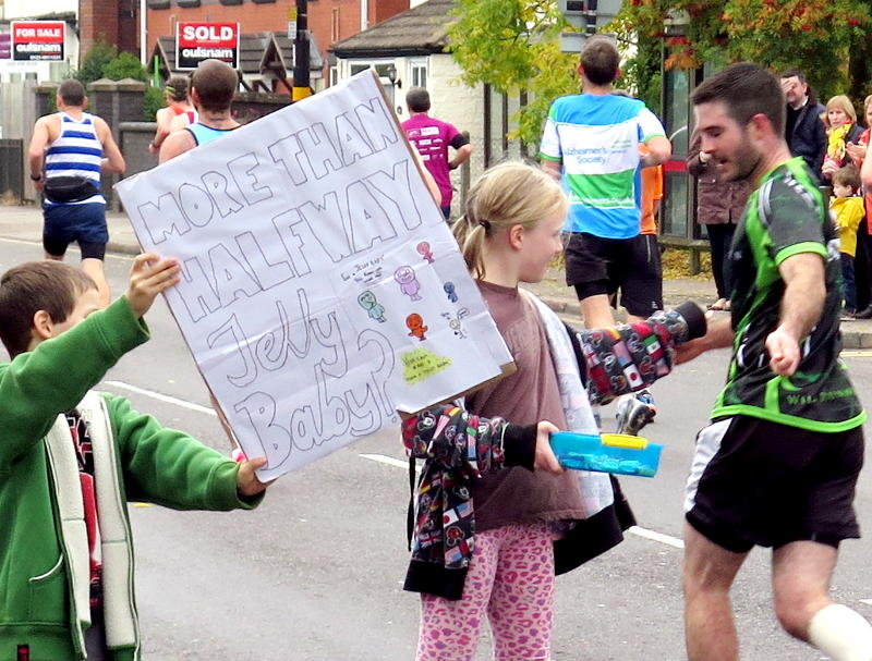 Holding up a banner - More than halfway - and offering a jelly baby to a runner
