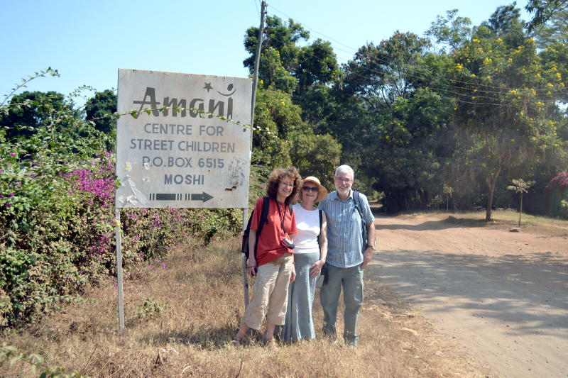 Christ Church members standing next to the Amani Children's Home sign