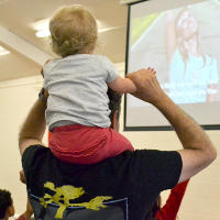 Sitting on an adult's shoulders at Messy Church