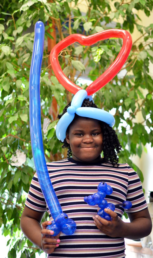 Carrying and wearing an assortment of balloon models