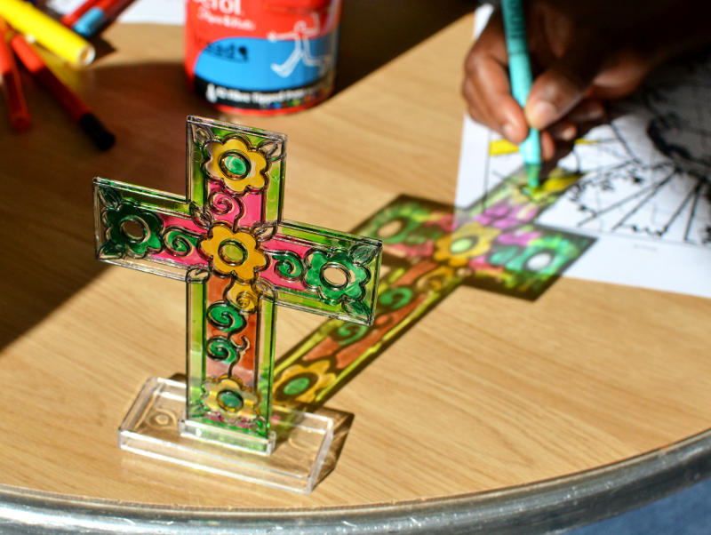 The sun shining on a stained glass cross