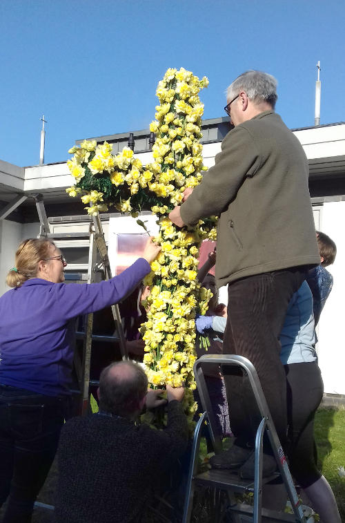 Decorating the cross outside our building with flowers at Easter