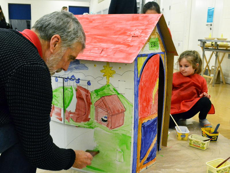 All ages working together to paint a cardboard stable