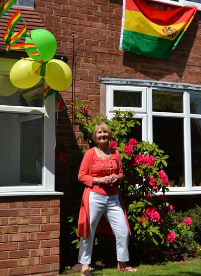 Margaret with Bolivian flags and coloured balloons outside her house