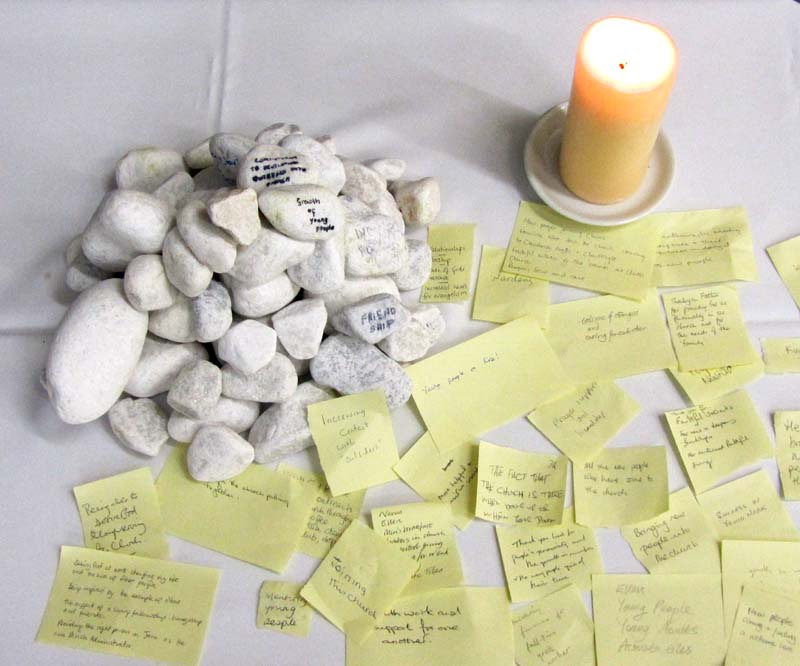A candle, small stones and sticky notes on a table