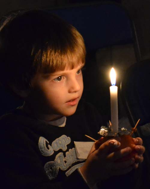A Christingle with lighted candle