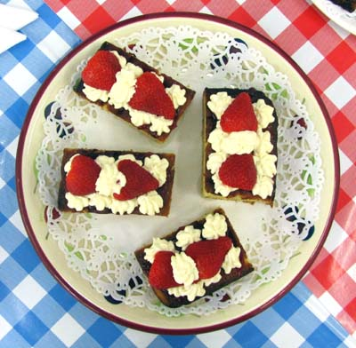 Looking down on a plate of strawberry-topped cakes
