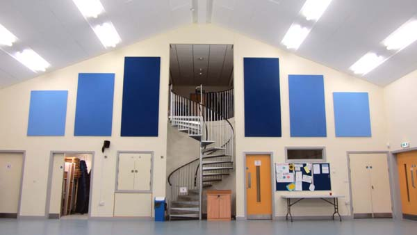 Looking towards the centre of the building. The kitchen hatch is on the left of the staircase, and the open door leads into one of the store rooms where chairs, tables and other equipment are kept. The large blue panels improve the acoustic performance of the hall