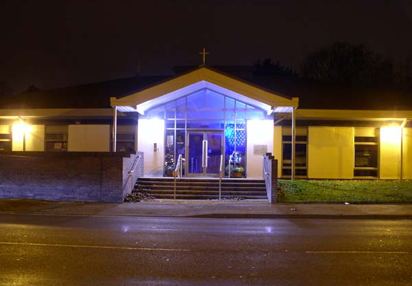 A modern church building at night with Christmas decorations visible through the glass doors