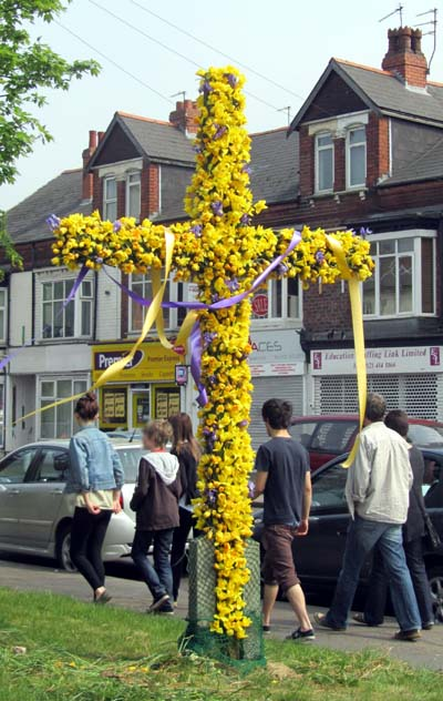 A cross by the roadside decorated with flowers