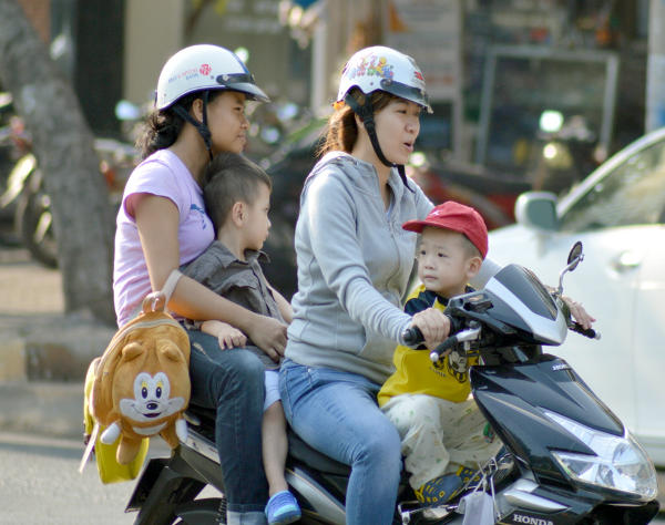 Riding a motorbike in Vietnam - only the adults wearing helmets