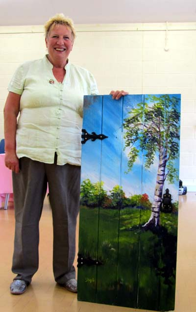Steph displays a painting of a tree made on an old door