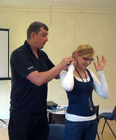 A policeman finds the pressure points under Ellen's ears