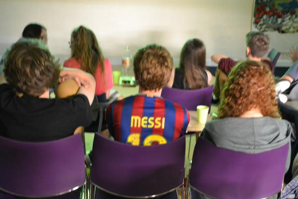 Watching a football match, wearing a Messi shirt
