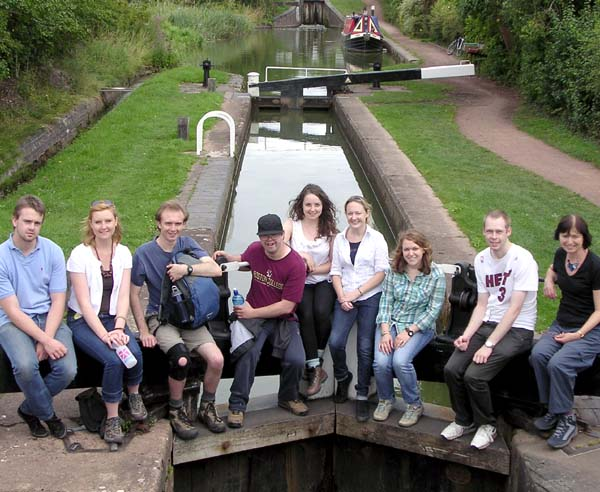 A group of young adults sitting on a canal lock gate